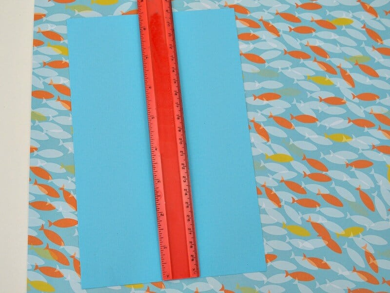 red ruler laying on blue paper on top of paper with fish design
