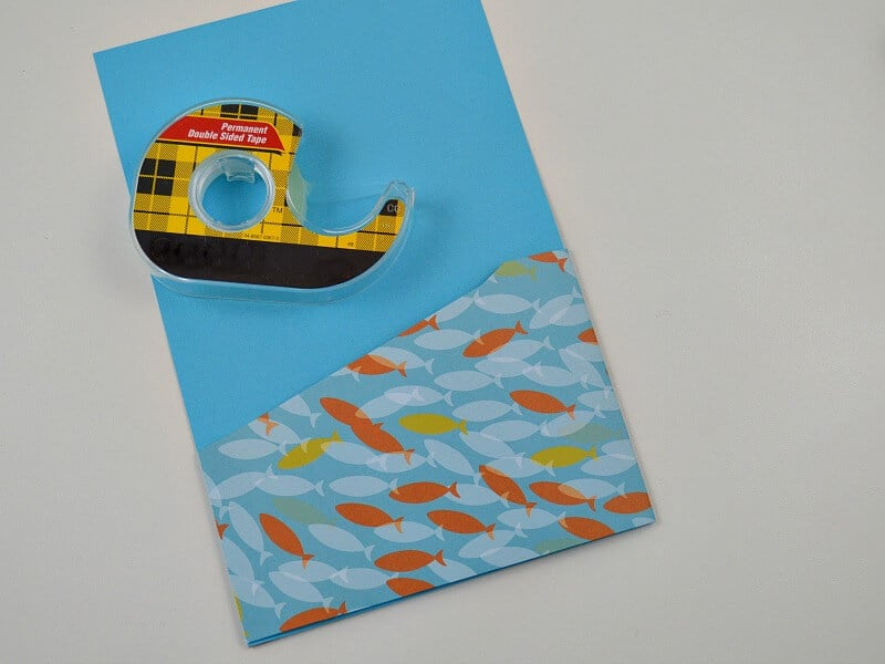 roll of tape on top of blue with fish images pocket