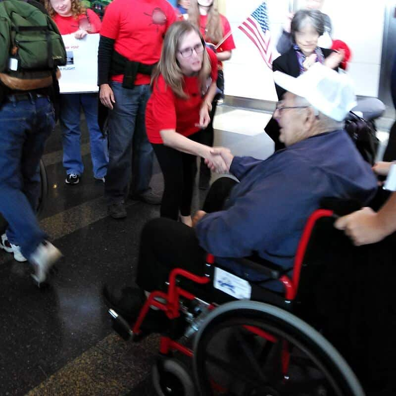 Crowd holding American flags and woman bending over to shake hand of older man in a wheel chair.