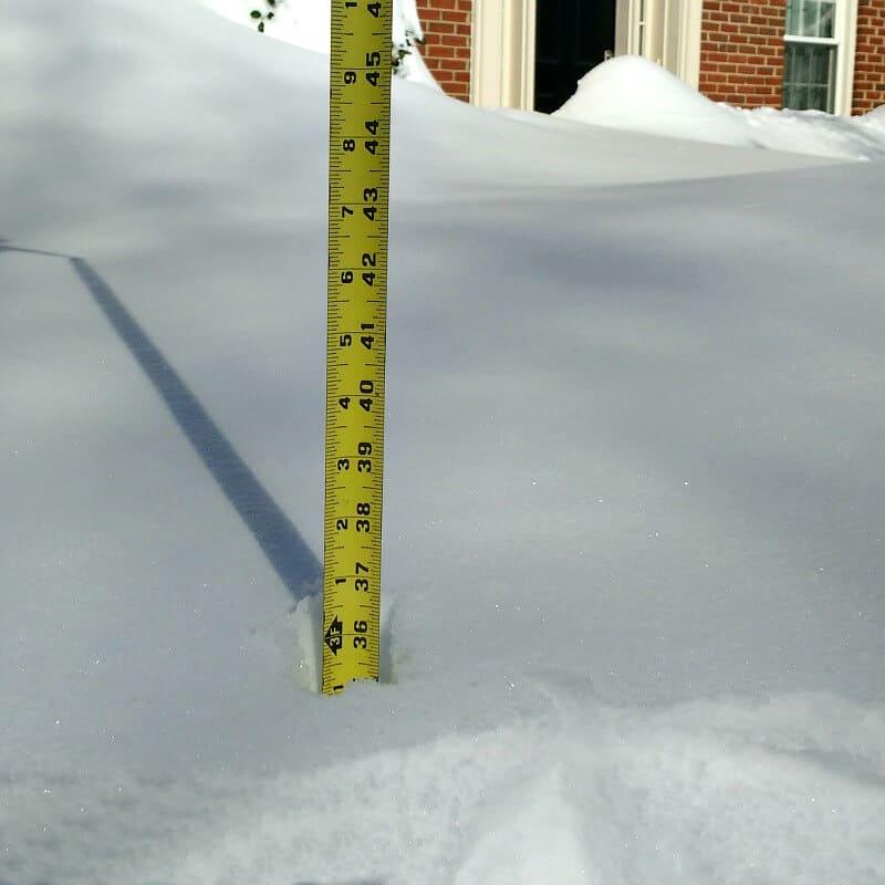 "yellow tape measure measuring  36"" deep snow"