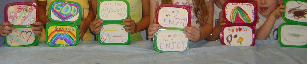 row of child holding boxes decorated with hand drawn pictures