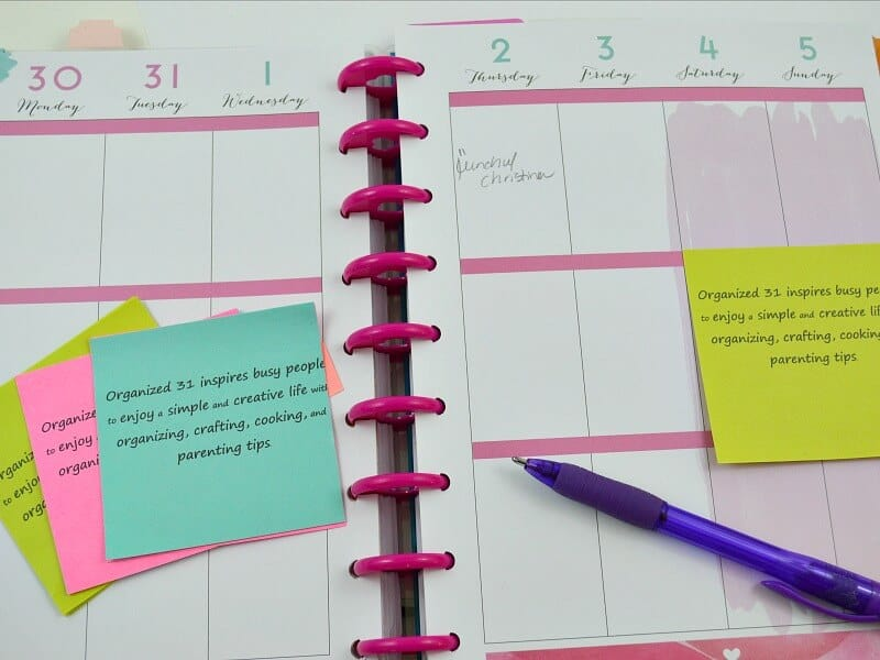 open planner with colorful sticky notes and blue pen
