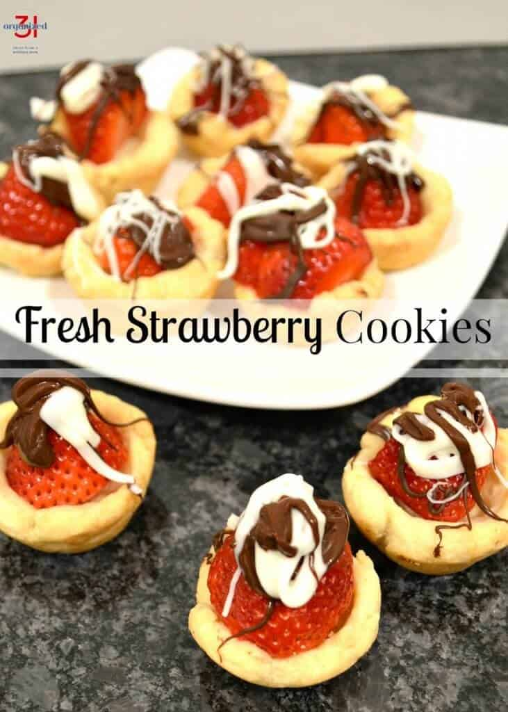 strawberry cookies with white and chocolate drizzles on plate with some cookies on counter in front