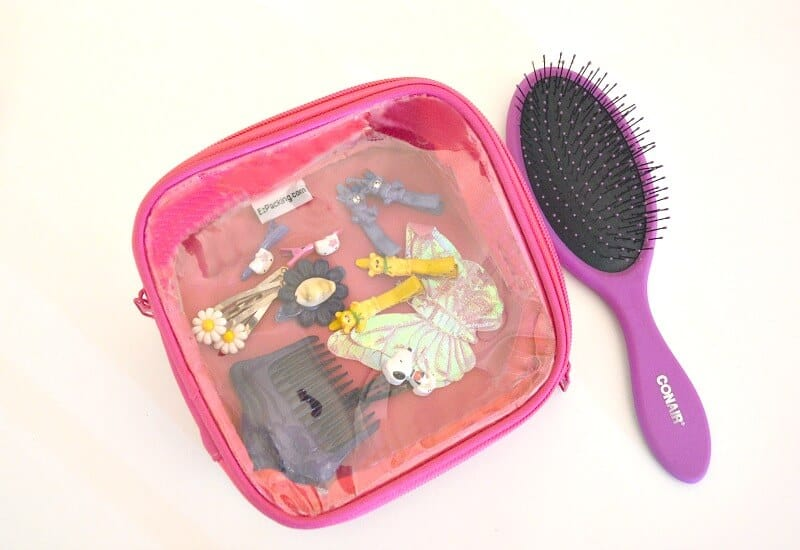 small pink packing cube with hair clips and pink hairbrush
