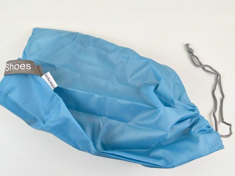 blue cloth shoe bag on white table