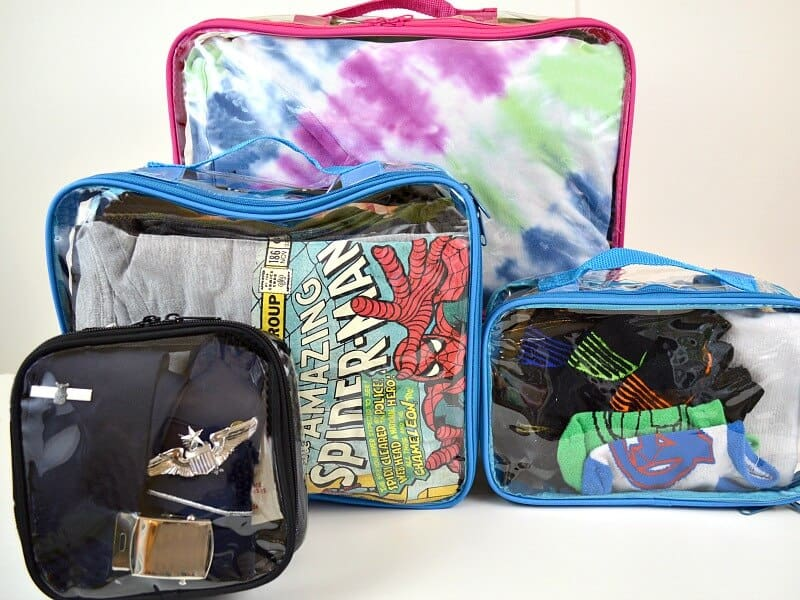 4 clear packing cubes with brightly colored clothing