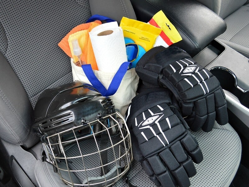 hockey helmet, hockey gloves and bag of cleaning supplies on passenger seat of car