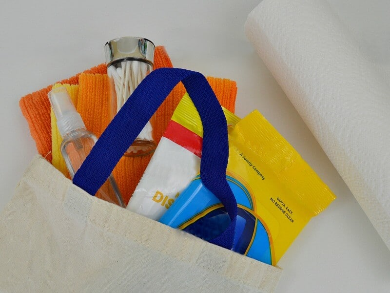 cloth bag filled with cleaning supplies next to roll of paper towels on table