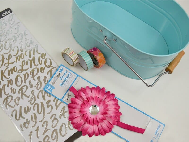 overhead view of blue caddy, with washi tape, sheet of letter stickers and pink flower on white table