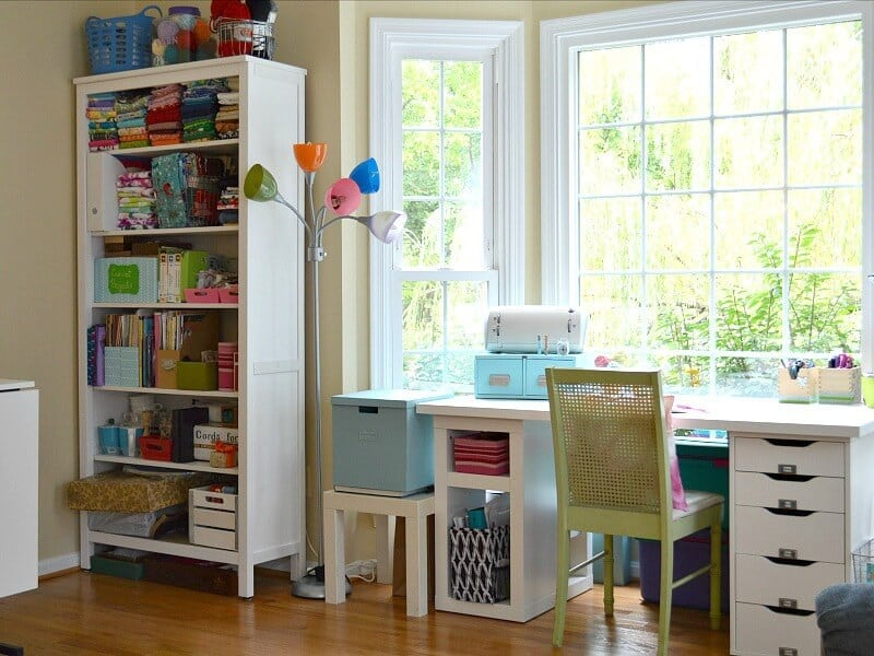 sleek organized craft room with white desk in front of window and white book case