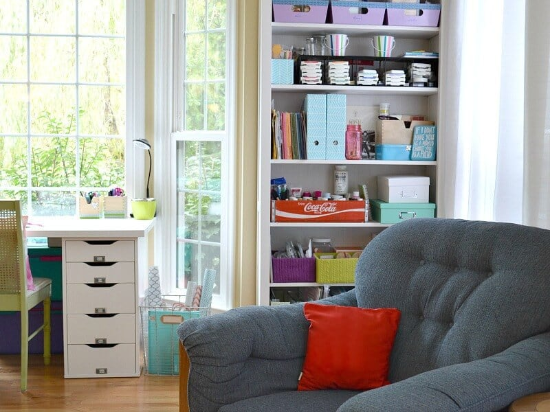 neatly organized craft room with white desk, white bookcase, and blue chair