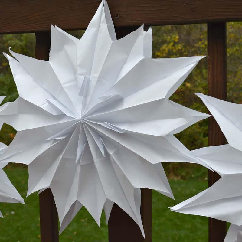 3 large white DIY paper stars hanging on deck railing