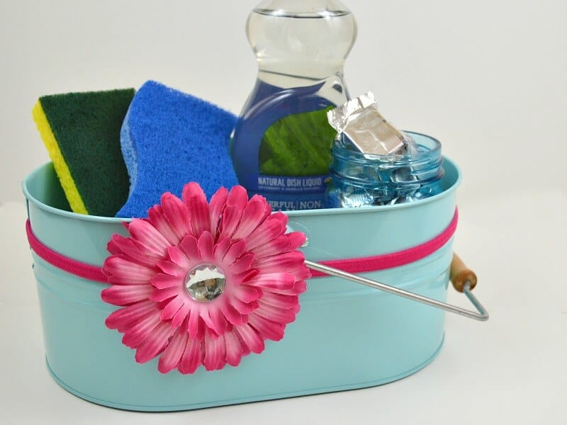 light blue caddy with pink flower holding sponges and liquid dish soap on white table