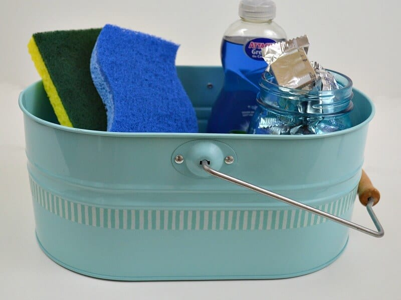 blue caddy with blue striped line with sponges and liquid dish soap and jar of dish washer tabs