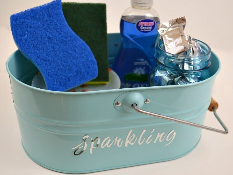 sponges, liquid soap, blue jar of silver packets in light blue caddy