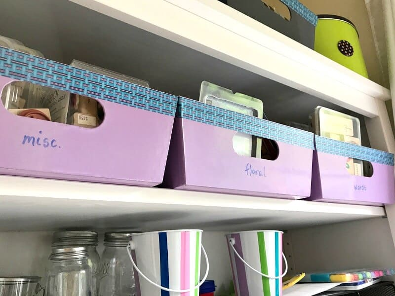 organizing boxes with stamps and ink, glass jars and metal boxes lower down