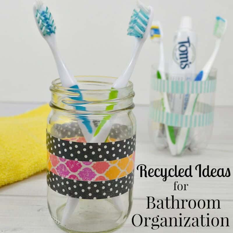 2 jars with washi tape stripes holding toothbrushes with yellow towel nearby