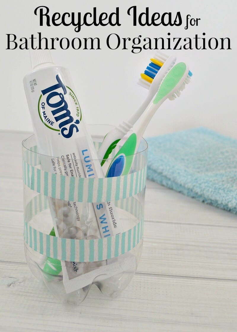 clear container with blue and white strips holding toothpaste and toothbrushes and blue hand towel on counter