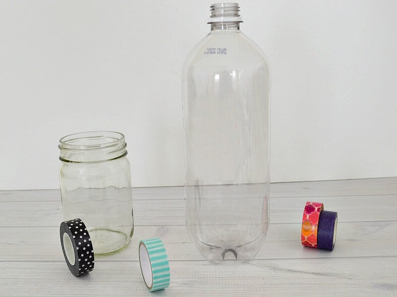 clear jar and soda bottle on white wood table with rolls of washi tape scattered around