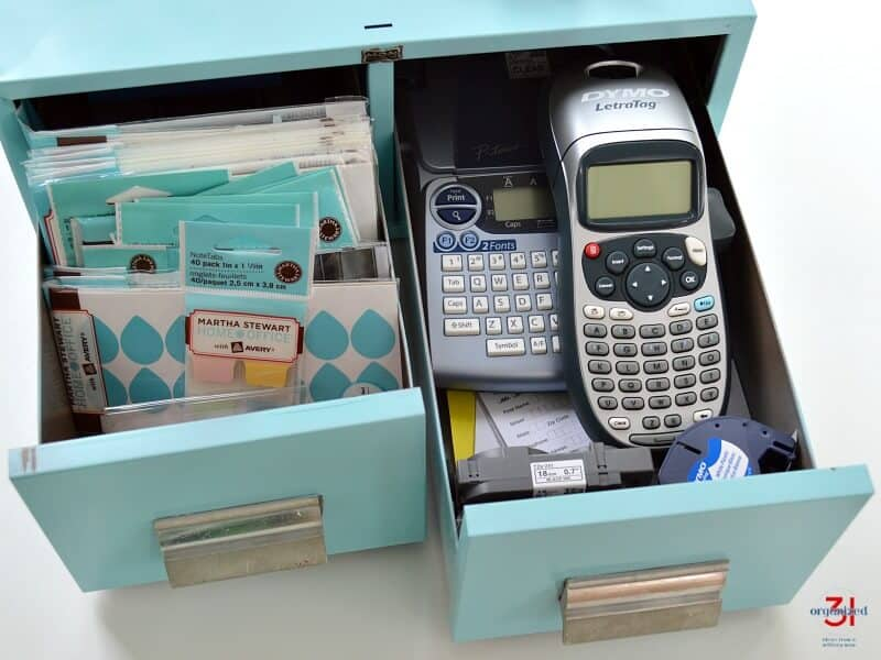 overhead view of open drawers of light blue library card drawers with labels and label makers in the drawers
