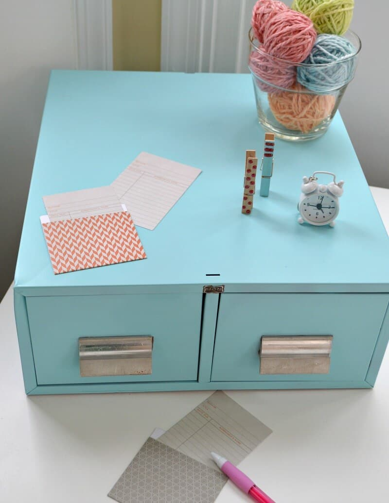 close up of light blue drawers with library card pockets, pink pencil and accessories