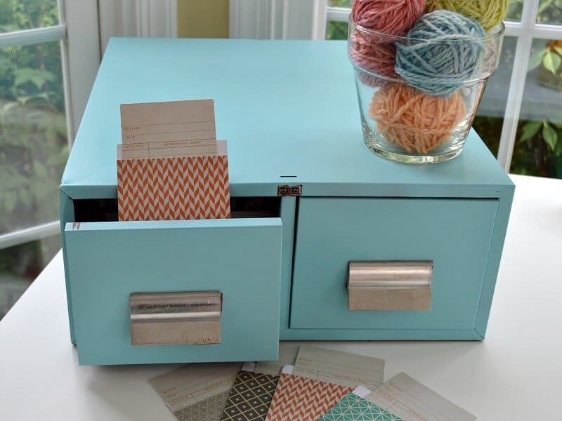 light blue sleek library card drawers with library card pockets on the table and one sticking out of open drawer