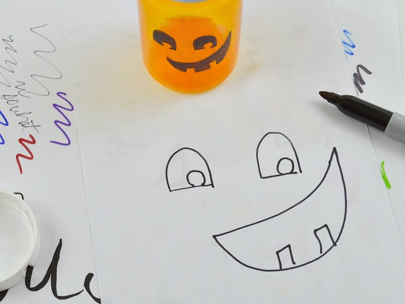 orange bottle with jack o'lantern face  and sharpie marker on top of paper with jack o'lantern face drawn on it