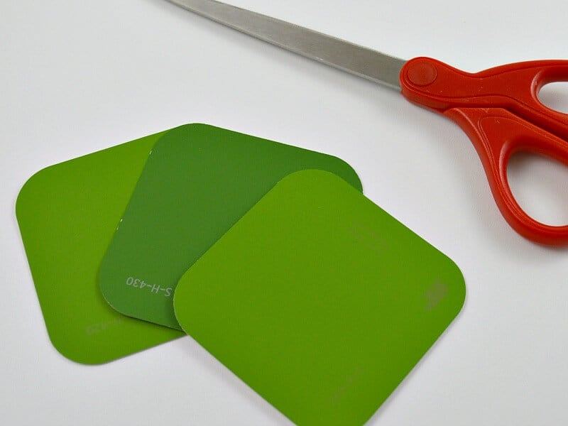 red scissors and 3 green squares of paper