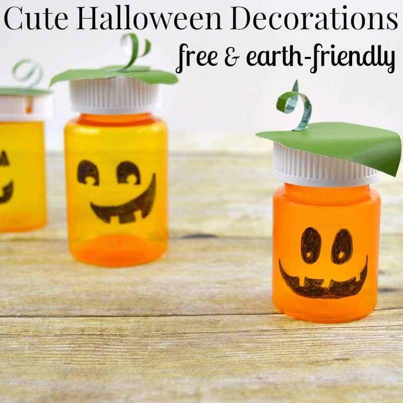 3 jack o'lanterns made from pill bottles on wood table with title text reading Cute Halloween Decorations Free and earth-friendly