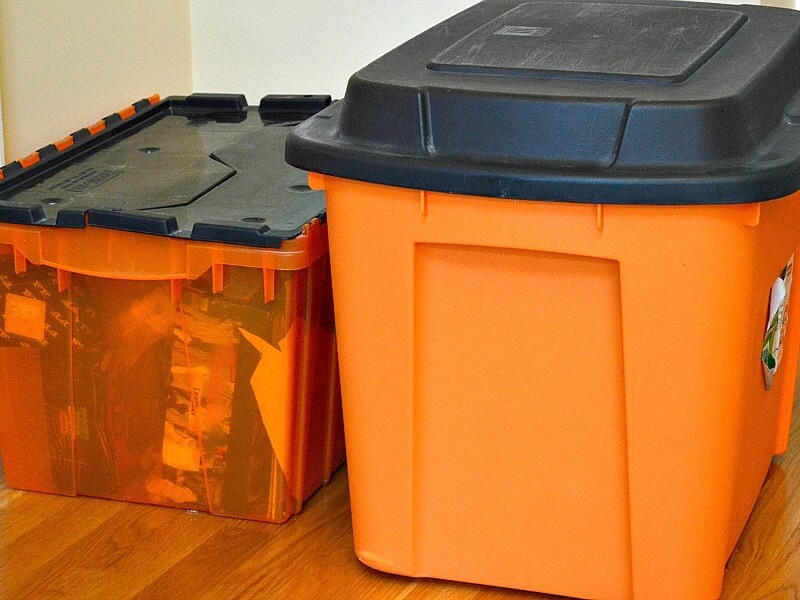 2 different style orange and black storage tubs next to each other on floor