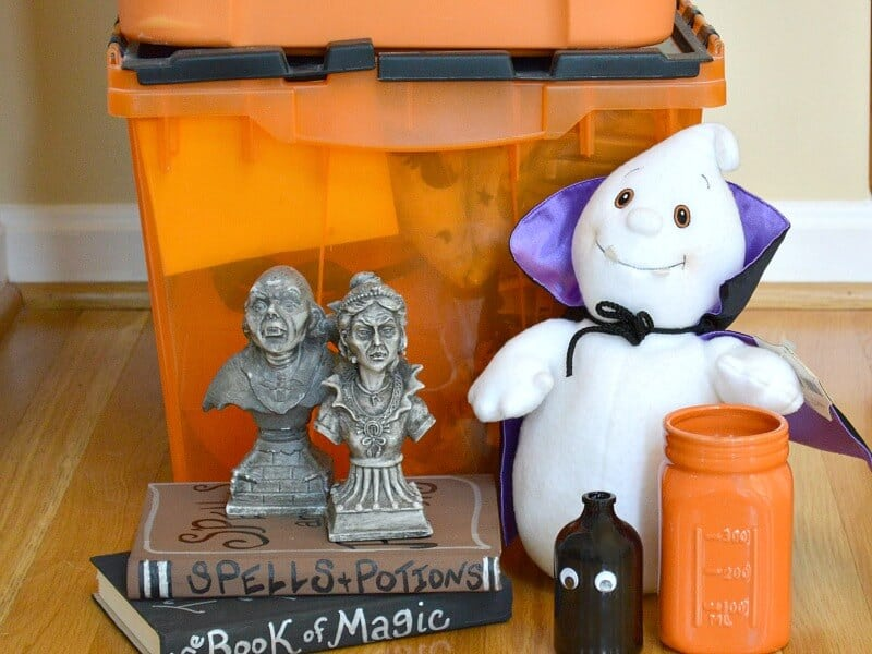 close up of variety of Halloween decorations on floor in front of stacked orange and black storage tubs