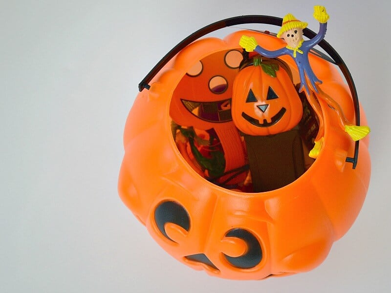 overhead view of Halloween-themed toys in a jack o'lantern treat bag