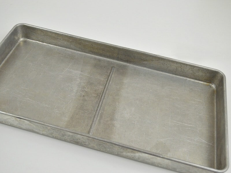 long silver aluminum pan with stain in middle