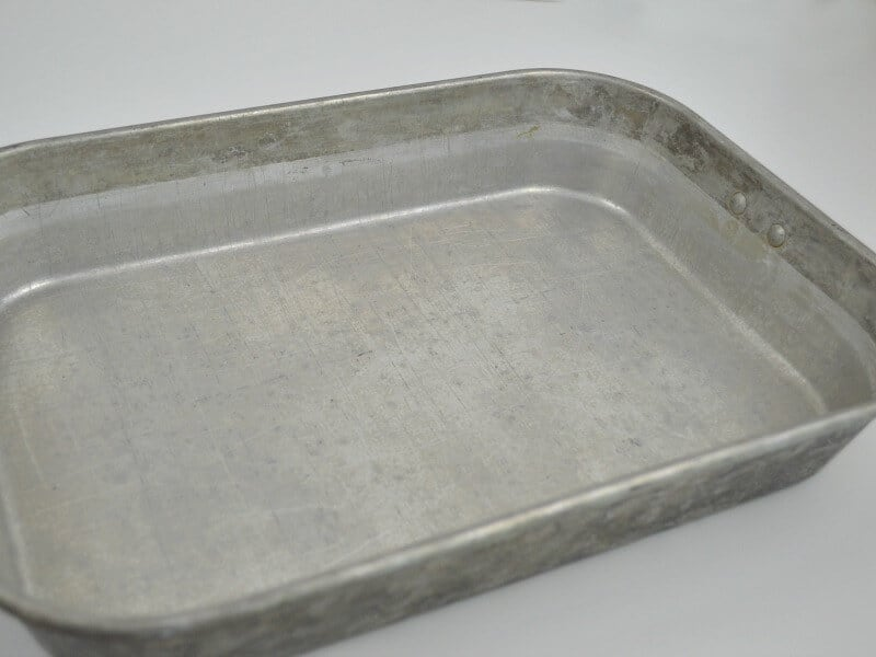 silver aluminum pan with stains at  top 1/2 inch by lip of pan