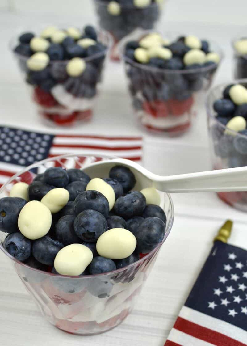 clear bowls of red, white and blue fruit on white wood table with American flags on table
