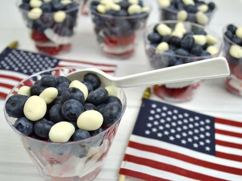 bowls of red, white and blue berries on white wood tables with 2 small American flags on table