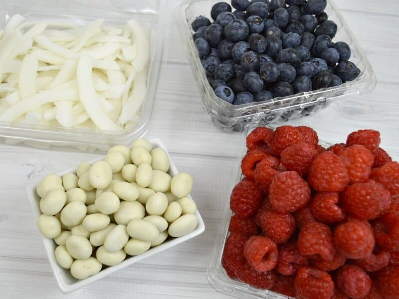 bowl of shredded coconut, bowl of blueberries, bowl of yogurt covered raisins and bowl of raspberries on white wood table