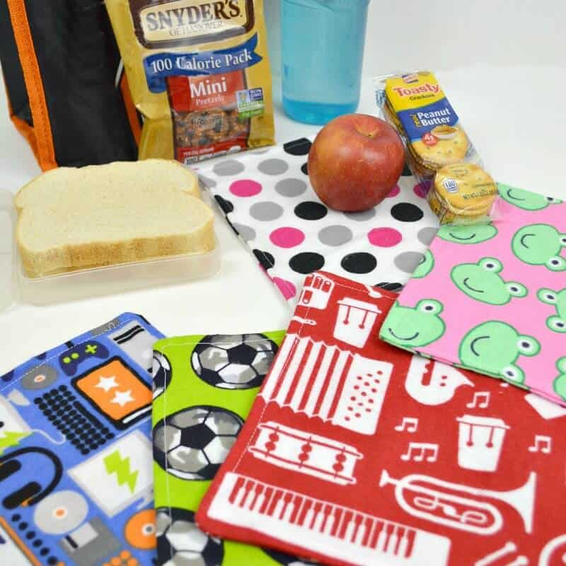 colorful cloth napkins fanned out on table with lunch bag, blue water bottle and food items on table
