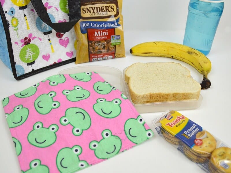 pastel colored lunchbox, food contents and pink cloth napkin with frogs on white table
