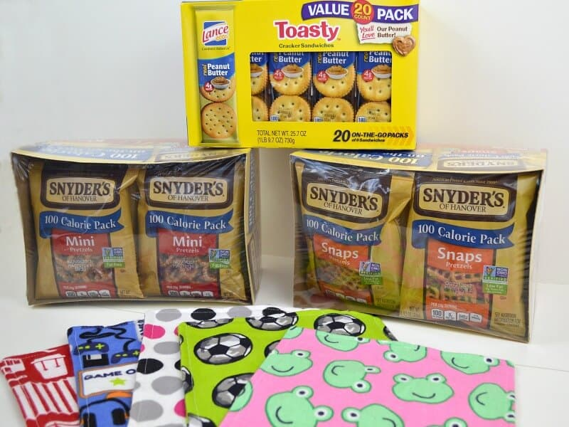 boxes of crackers and snack pretzels stacked with colorful cloth napkins in front
