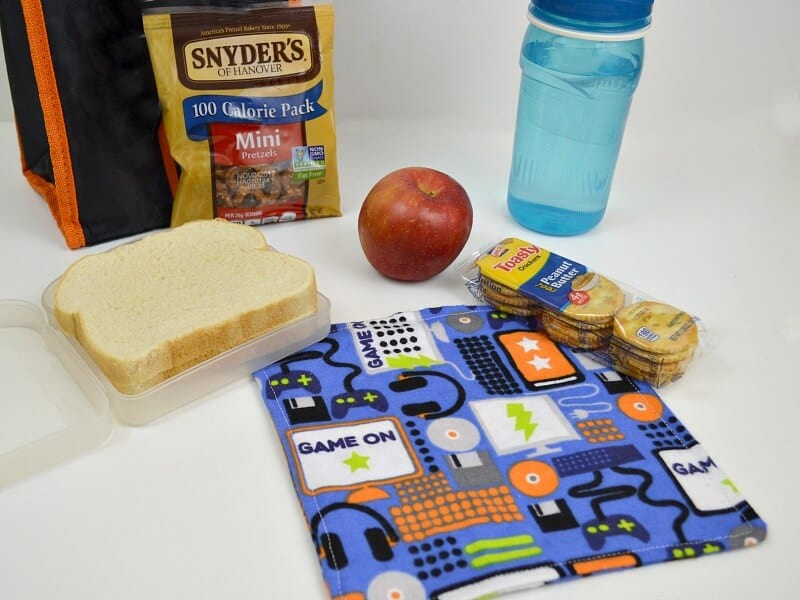 blue napkin with headphones, screens and keyboards and lunchbox, water bottle and food items on white table