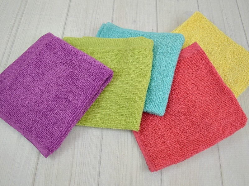 stack of colorful wash cloths on white wood table