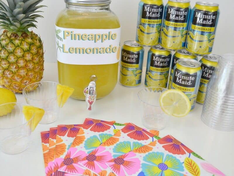 pineapple, beverage dispenser with yellow liquid and cans of lemonade with cups and floral napkins