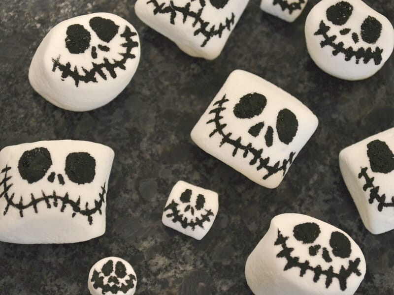 overhead view of different sizes of marshmallows with skeleton faces on black counter