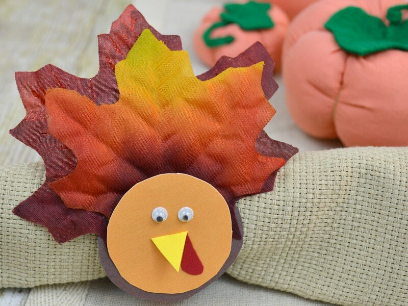diy turkey napkin holder on tan napkin with fabric pumpkins in the background