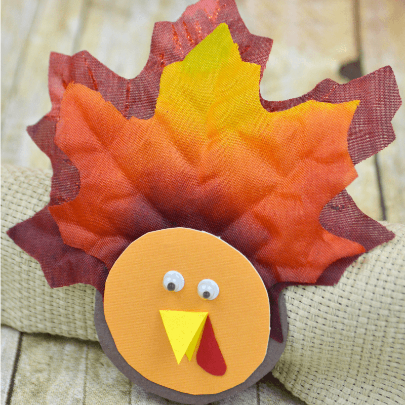 DIY turkey napkin ring on tan napkin laying on wood table