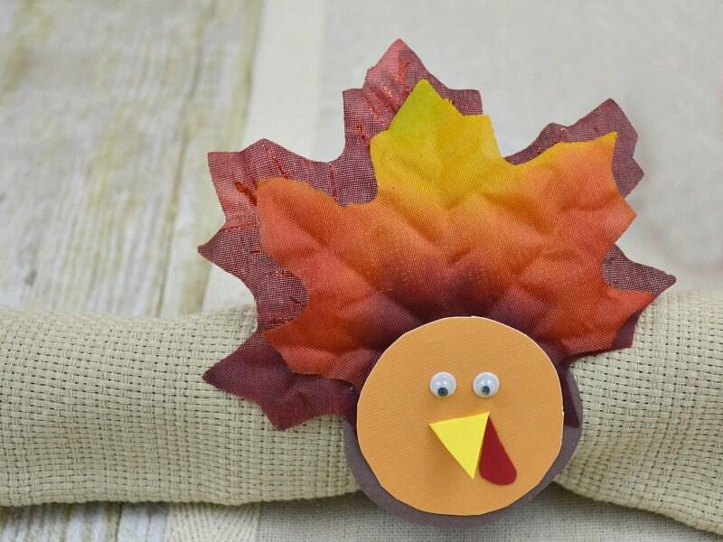 close up of turkey napkin holder on tan napkin on wood table