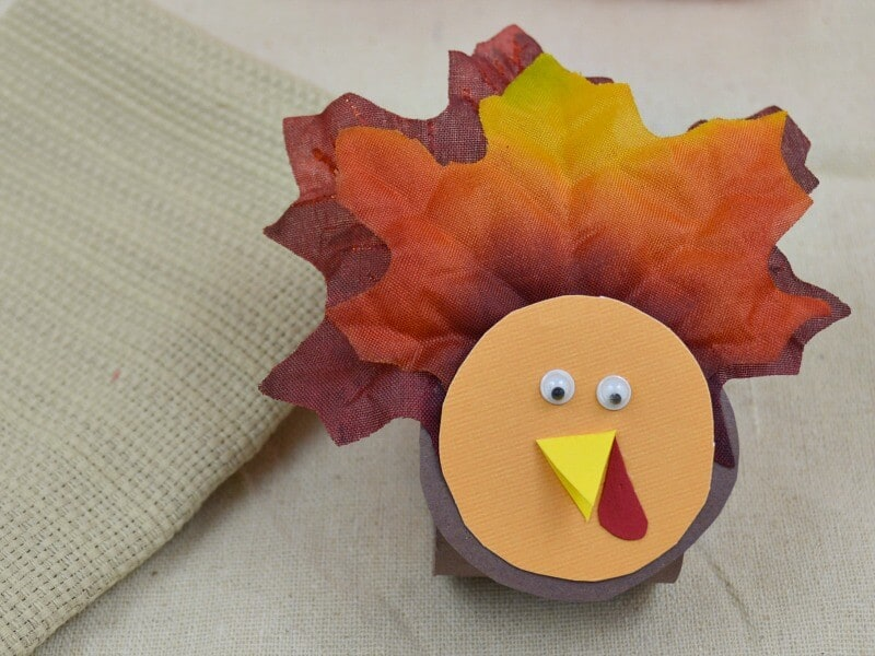 close up of face of turkey napkin ring holder with napkin in background
