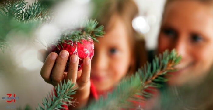 close up of mother and child reaching for red Christmas ball on tree