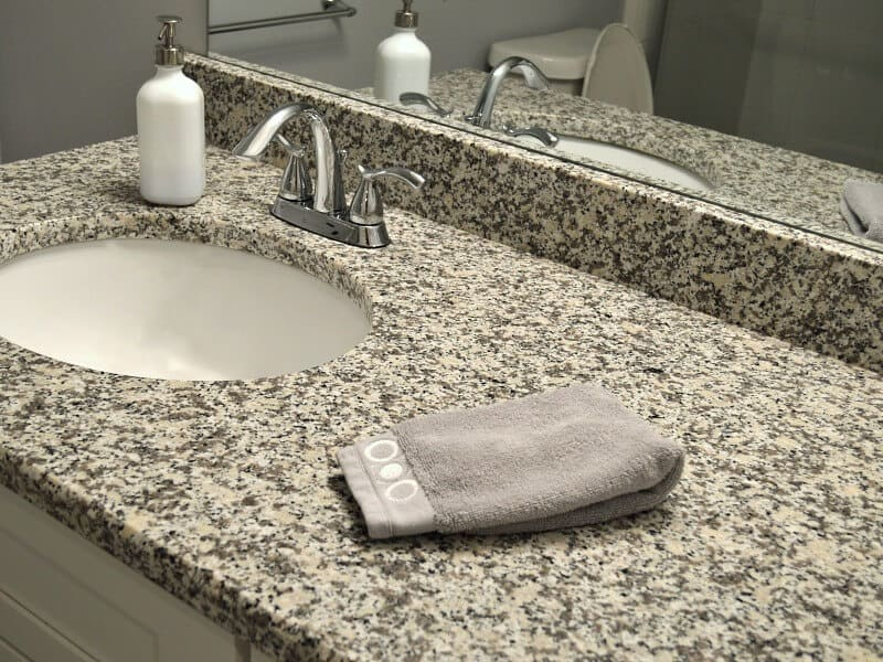 grey towel by bathroom sink with black, grey and white speckled counter top